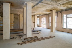 Large room during the repair. Pipes lie on a construction site. Building is ready for decoration. Preparation for communications. Engineering communications in a building under construction