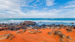 Large round stones on the shore are washed by the waves of the ocean. The sand on the shore is bright red.