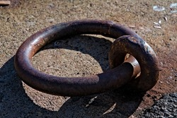 Large rusted iron ring used for mooring ships in the port.