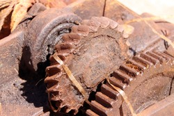 Large rusty corroded gearwheels at left behind industrial park. Weathered mechanics on sunny day.