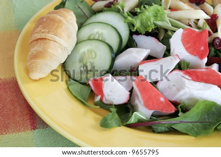 large salad with artificial crabmeat, cucumbers,spinach,lettuce,pasta,croissant
