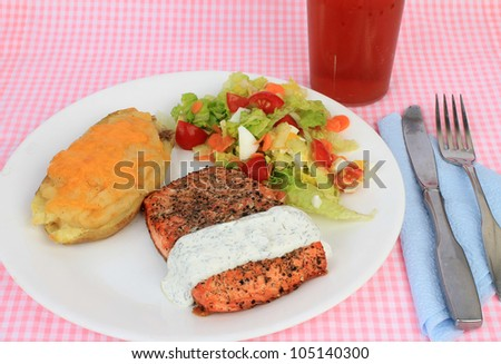Large Salmon Steak coated with spices and grilled to perfection served with special tartar sauce, twice-baked potato and mixed salad and sweet iced tea.  Pink gingham place mat as background.