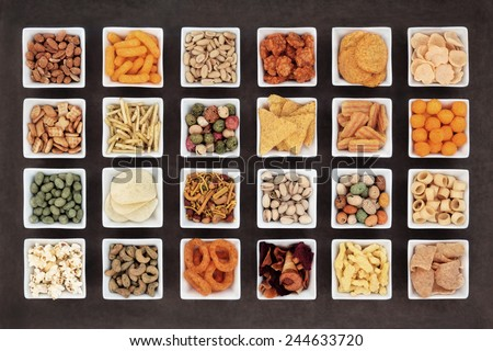 Large savoury snack food selection in square porcelain bowls.