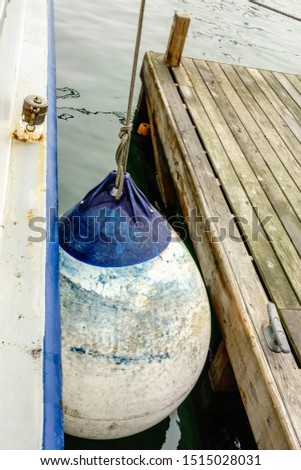 Large scraped bumper hanging between side of boat and wooden dock in marina, for themes of separation and protection, friction, wear and tear #1515028031