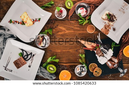 Large selection of desserts and sweets. On a wooden background. Top view. Copy space.