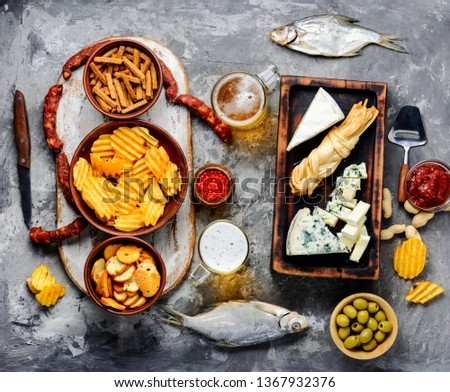 Large selection of snacks for beer. Set of cheeses, fish, chips and snacks.Beer and snacks
