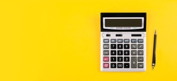 Large silver calculator with gray and black buttons and black pen on a yellow background. Conceptual photo of calculations, accounting, computing, profit, loss, tax with place for text.