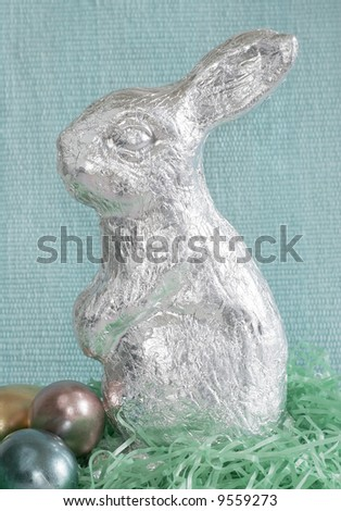 large silver rabbit with eggs sitting in artificial grass with blue background