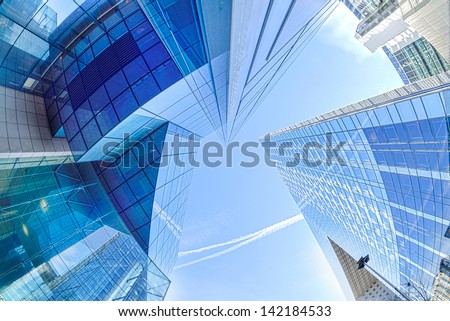 Large skyscrapers shot with a fisheye lens La Defense major business district near Paris, France . Abstract business background with office building skyscrapers