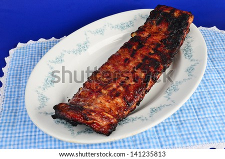 Large slab of charbroiled pork ribs on platter against blue background. - stock photo