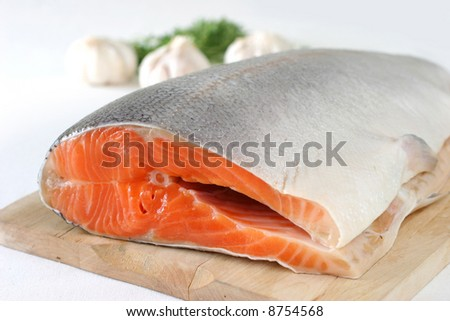 Large slab of tail portion of fresh Atlantic salmon on wooden chopping board
