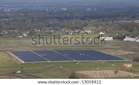 large solar energy farm (3.3MW) at foothills campus of Colorado State University, aerial view from a mountain ridge with a hazy view of Fort Collins city in background