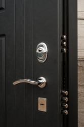 Large solid lock in a metal black door close-up