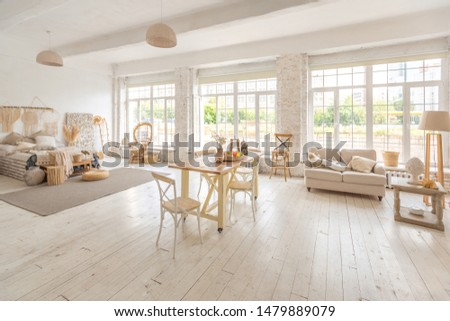 Large spacious room with a trendy loft design. The bright, open-plan room includes a sitting area, a bedroom area and a dining area. huge windows and stylish wicker light furniture inside