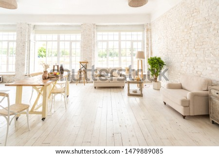 Large spacious room with a trendy loft design. The bright, open-plan room includes a sitting area, a bedroom area and a dining area. huge windows and stylish wicker light furniture inside #1479889085