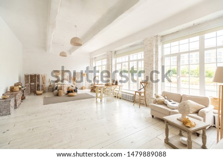Large spacious room with a trendy loft design. The bright, open-plan room includes a sitting area, a bedroom area and a dining area. huge windows and stylish wicker light furniture inside #1479889088