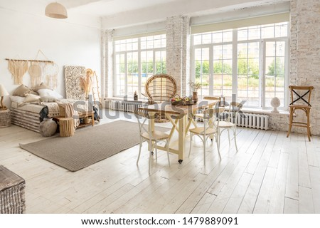 Large spacious room with a trendy loft design. The bright, open-plan room includes a sitting area, a bedroom area and a dining area. huge windows and stylish wicker light furniture inside #1479889091