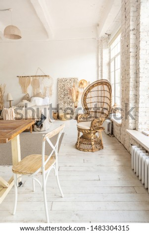 Large spacious room with a trendy loft design. The bright, open-plan room includes a sitting area, a bedroom area and a dining area. huge windows and stylish wicker light furniture inside #1483304315