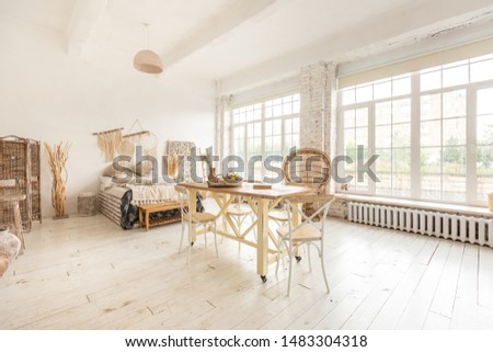 Large spacious room with a trendy loft design. The bright, open-plan room includes a sitting area, a bedroom area and a dining area. huge windows and stylish wicker light furniture inside #1483304318