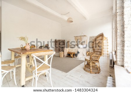 Large spacious room with a trendy loft design. The bright, open-plan room includes a sitting area, a bedroom area and a dining area. huge windows and stylish wicker light furniture inside #1483304324