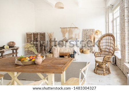 Large spacious room with a trendy loft design. The bright, open-plan room includes a sitting area, a bedroom area and a dining area. huge windows and stylish wicker light furniture inside #1483304327