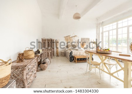 Large spacious room with a trendy loft design. The bright, open-plan room includes a sitting area, a bedroom area and a dining area. huge windows and stylish wicker light furniture inside #1483304330