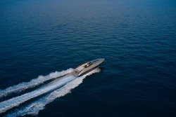 Large speed boat moving at high speed side view. Drone view of a boat  the blue clear waters at sunset. The boat is gray-blue combined color. Top view of a boat sailing to the blue sea.