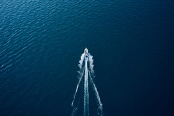 Large speedboat moving at high speed at sunset. Travel - image. Drone view of a boat the blue clear waters. Aerial view luxury motor boat.