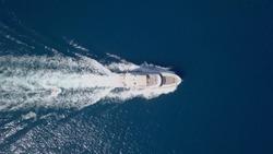 Large speedboat roaring across the Mediterranean Sea - Top down aerial image.