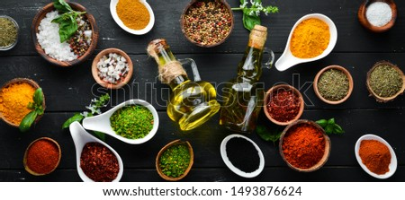 Large spice and herb collection in bowls and spoons. Indian spices. On a black wooden background. Top view.