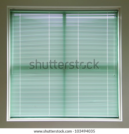 Large square window covered with green blinds.