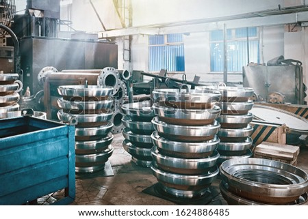 Large steel round discs for the production of valves for the gas and oil industries in an engineering plant. Industrial background.