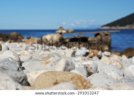 Large stone pebbles on the shore of the sea of the Bay, a small zone of sharpness, springboard