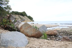 Large stones on a sandy beach with a hill covered with trees