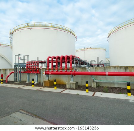 large storage tanks for oil and petrol in the amsterdam harbor area. The red pipelines are for water supply in case of an fire emergency