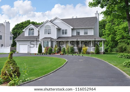 Large Suburban McMansion Home with blacktop circular driveway in residential neighborhood in USA
