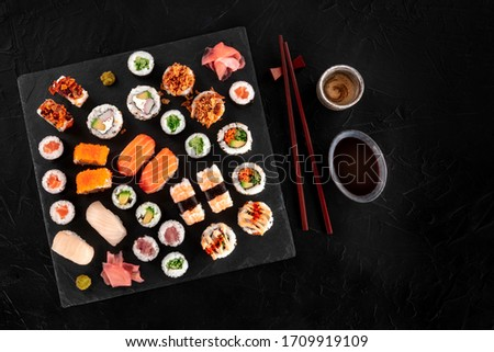 Large sushi set, shot from the top on a black background. An assortment of various maki, nigiri and rolls with sake, soy sauce, and chopsticks