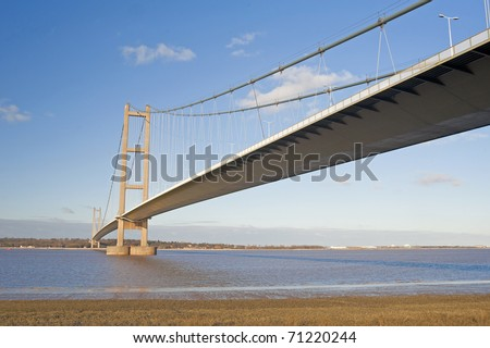 Large suspension bridge spanning a wide river on a clear day