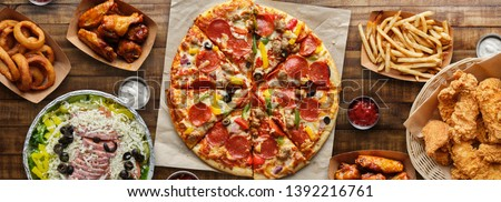 large table of assorted take out food such as pizza, french fries, onion rings, fried chicken and chicken wings ストックフォト ©