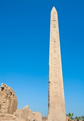 Large tall ancient egyptian obelisk at the temple of Karnak in Luxor with hieroglyphic carvings on blue sky background
