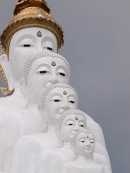 large tall white five buddha faces crop closeup of outdoor statue sculpture in contemporary THAI buddhism art style in a buddhism temple in THAILAND