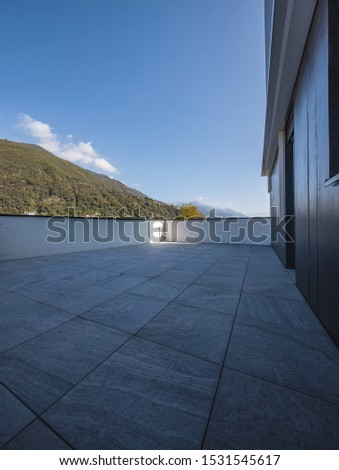 Large terrace with large marble tiles overlooking the Swiss hills in Ticino. Nobody inside. Sunny day, blue sky