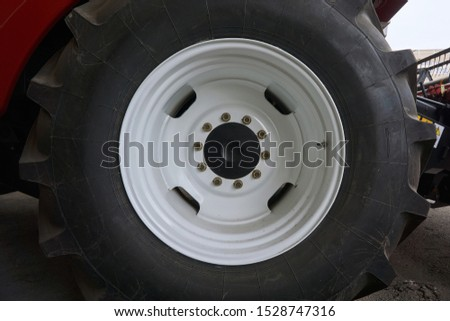 large tires with a large tread on a new agricultural tractor after assembly at the plant on a sunny day
