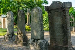 Large tombstones in a row, old gravestones with moss growing on them. In summer sunlight at a cemetery in Sweden