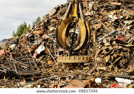 Large tracked excavator working a steel pile at a metal recycle yard with a magnet. - stock photo