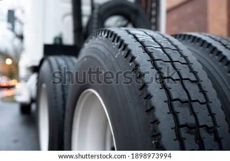 Large tread with grooves and special pattern for durable traction on big rig semi truck tractor tires on paired wheels ensures safe grip when transporting heavy cargo at any weather condition Stockfoto ©