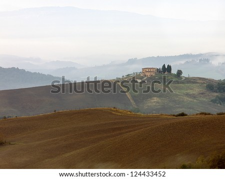 Large Tuscan villa sits atop of the hillside in the beautify Italian landscape picture.