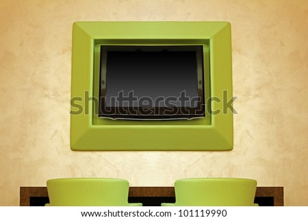 Large TV screen in modern interior with green chairs