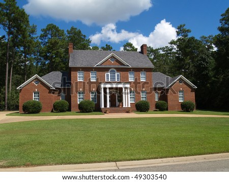 Large two story red brick residential home with side entry garage.