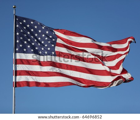 "Large U.S. Flag ""Old Glory"" blowing in a strong wind on a cloudless day"